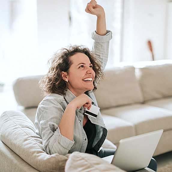 Smiling woman with fist in air, laptop open