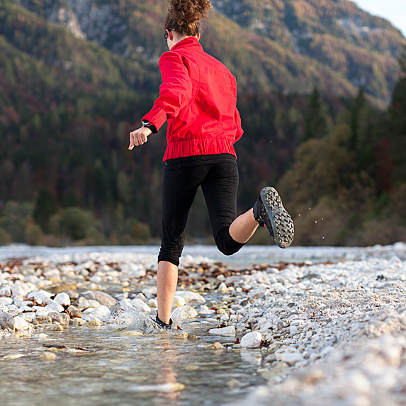 Woman running outside by stream
