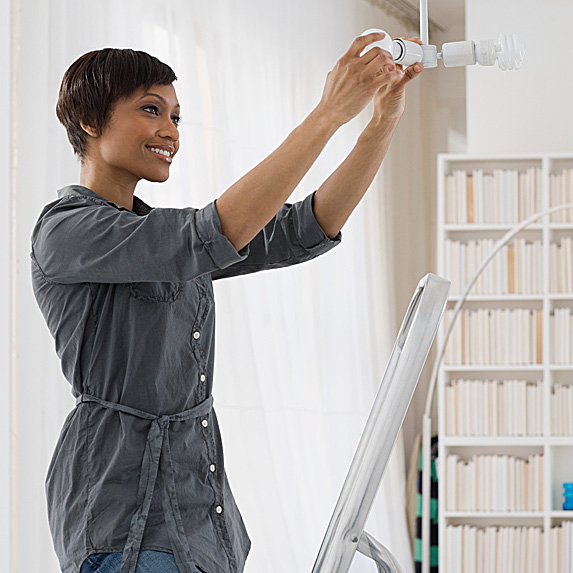 Woman changing light bulb of hanging fixture
