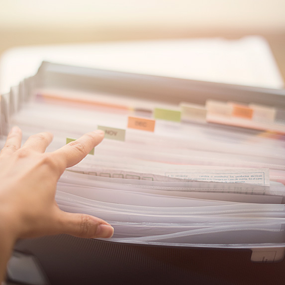 Woman's hand looking through filing system