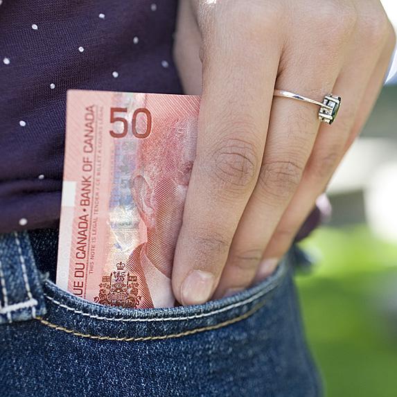 Woman putting $50 bill in pocket