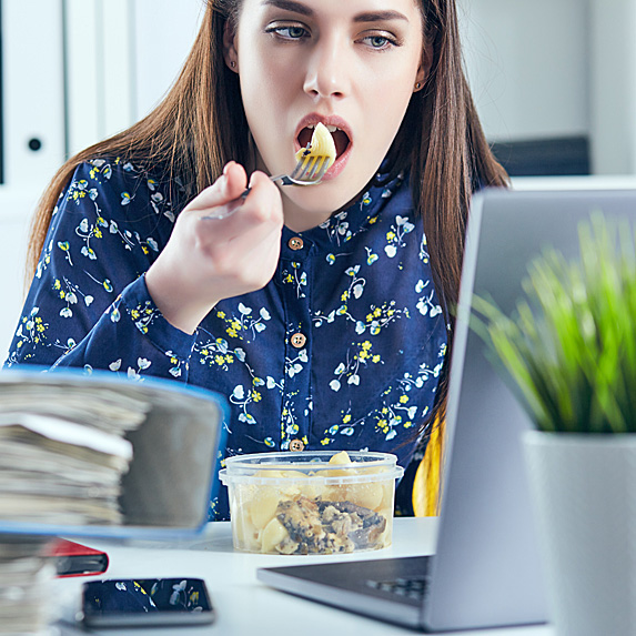 Woman eating homemade lunch at desk