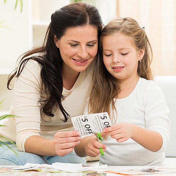 Mother and daughter clipping coupons