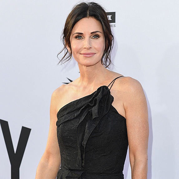 Courteney Cox smiles in a black dress
