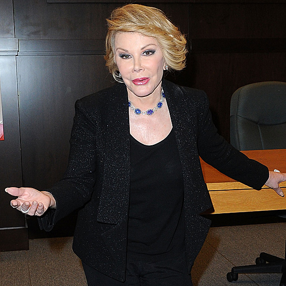 Joan Rivers stands with one hand outreached to the camera