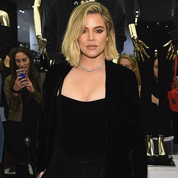 Khloe Kardashian wears her hair in a side part and a diamond necklace
