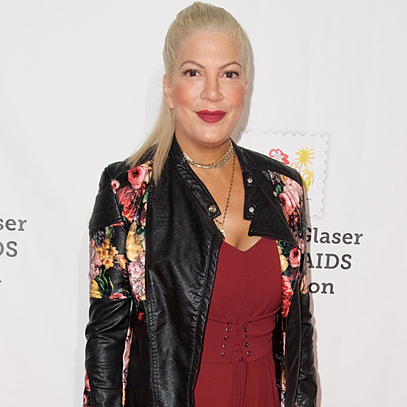 Tori Spelling wears a leather jacket over a red jumpsuit