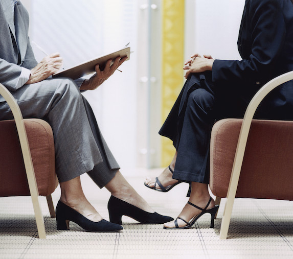 An interviewer wearing closed-toe shoes sits across from the interviewee, who is wearing open-toed sandals