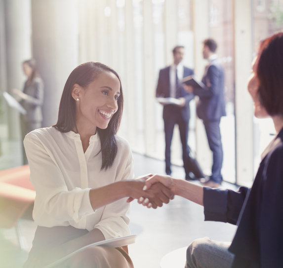 Smiling businesswoman shakes hands with another woman in the lobby of a corporate building