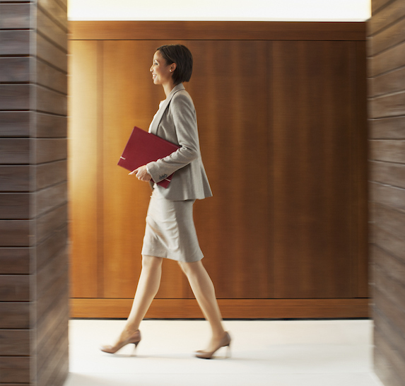 Businesswoman holds a folder while walking in corridor