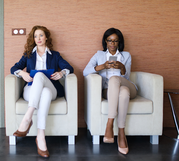 Two businesswomen sit in a waiting room