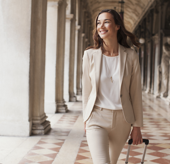 Smiling woman wears a pantsuit and walks through an outdoor corridor