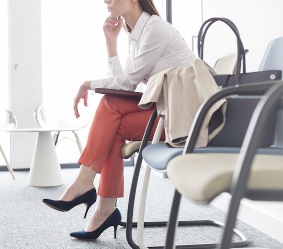A well-dressed woman sits in the waiting area of an office environment