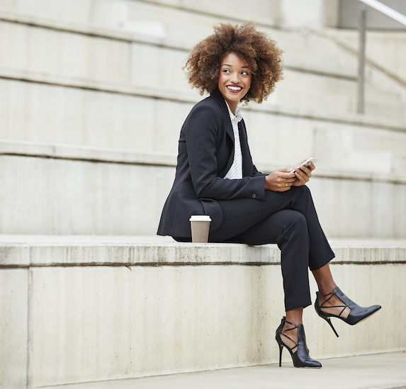 Businesswoman sits on steps outdoors, having a coffee