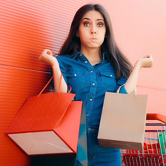 Frustrated woman holding shopping bags