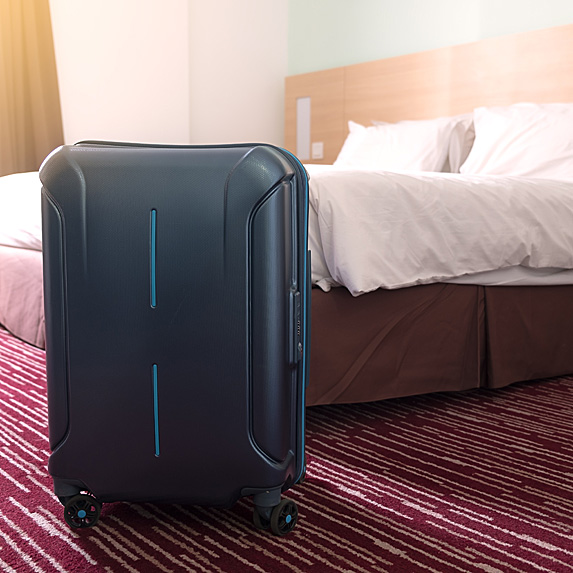 Suitcase next to hotel bed