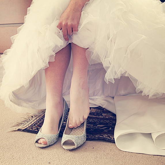 Bride slipping shoes on