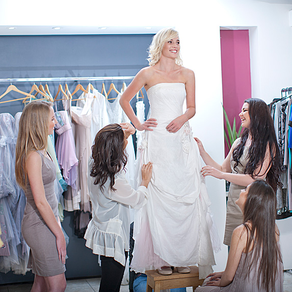 Woman trying on wedding dress with friends watching