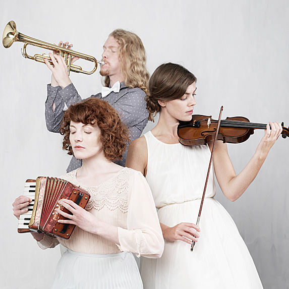 Man holding trumpet, woman holding accordian, another woman holding violin