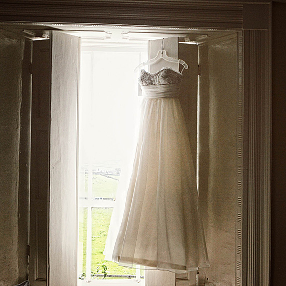 Wedding dress hanging by window