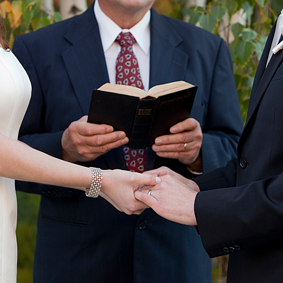 Officiant holding book in front of couple holding hands