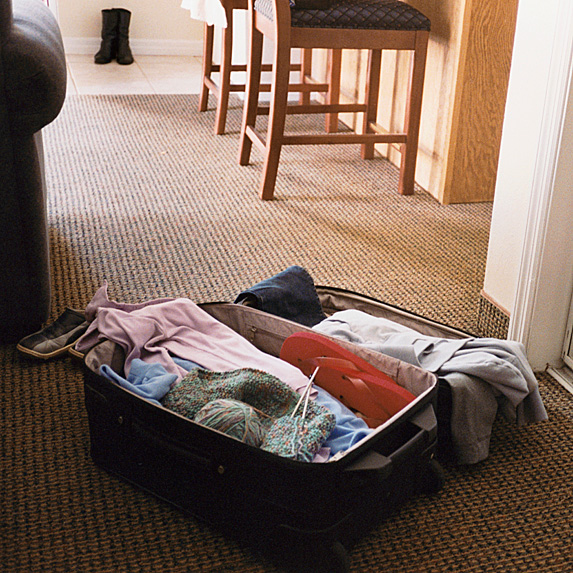 Open suitcase on floor, full of clothes