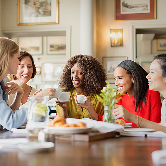 Five women sitting around table eating and drinking