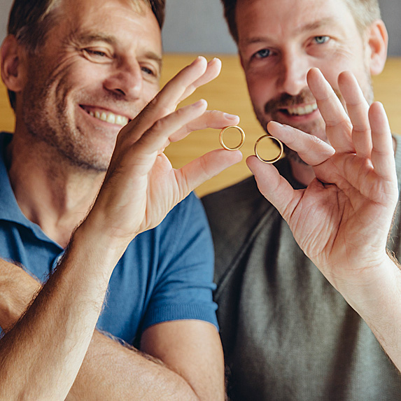 Two men holding wedding bands