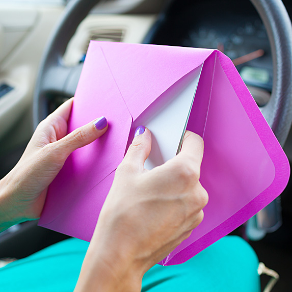 Woman in car putting card in envelope