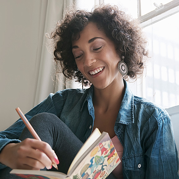 Woman smiling and writing in notebook