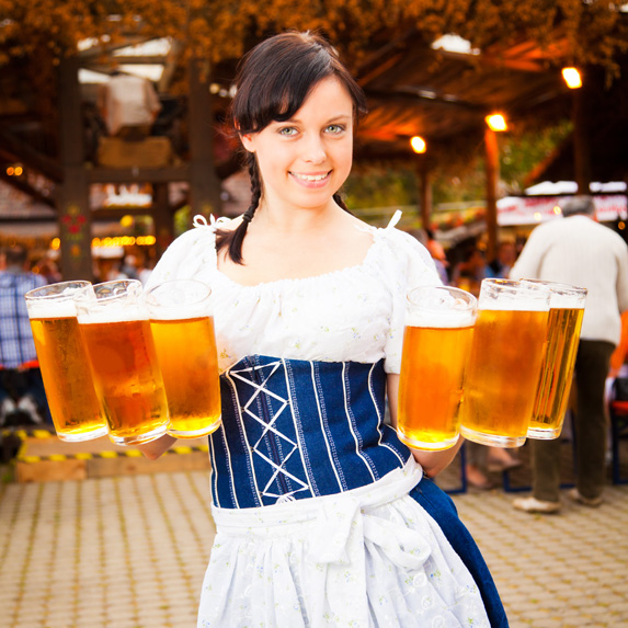 Person holding mugs of beer at Oktoberfest in Munich