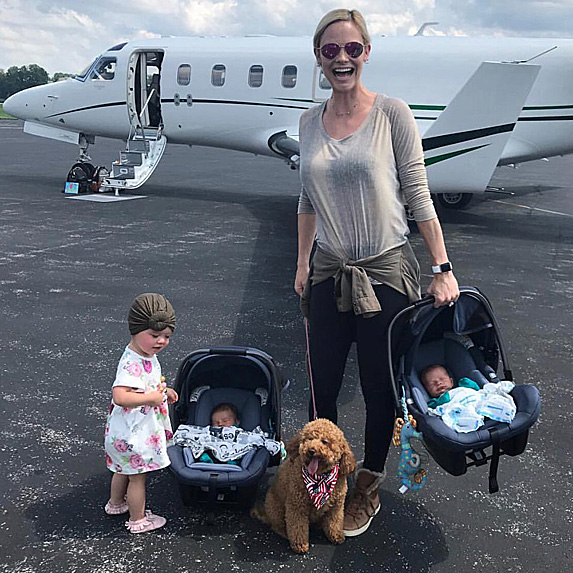Meghan King Edmonds in front of plane with three kids and dog
