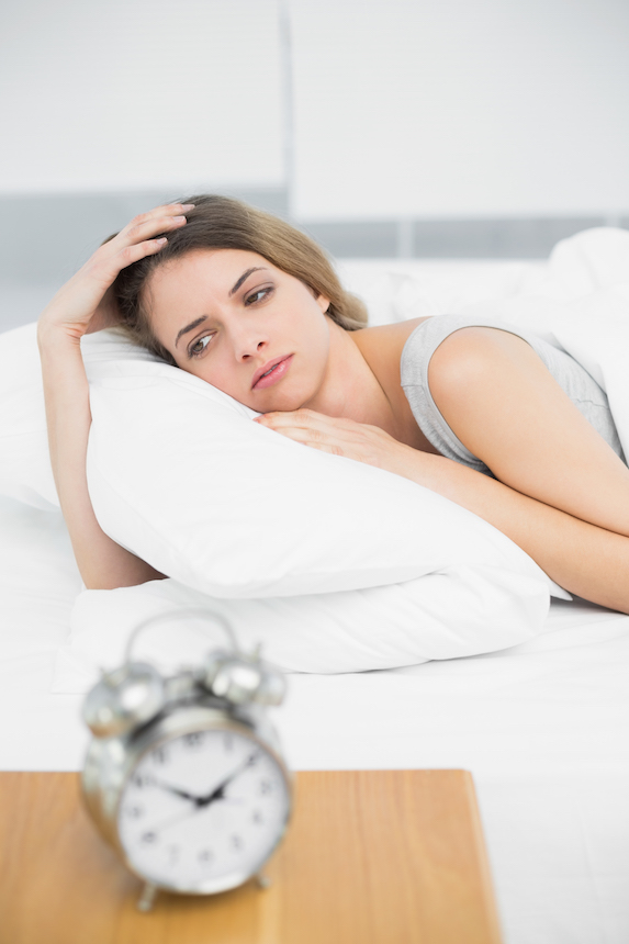 Woman lies in bed looking anxious, while a clock sits on the nightstand