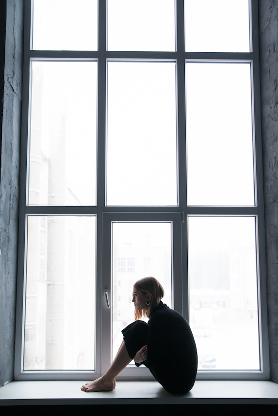 Woman sits at a window