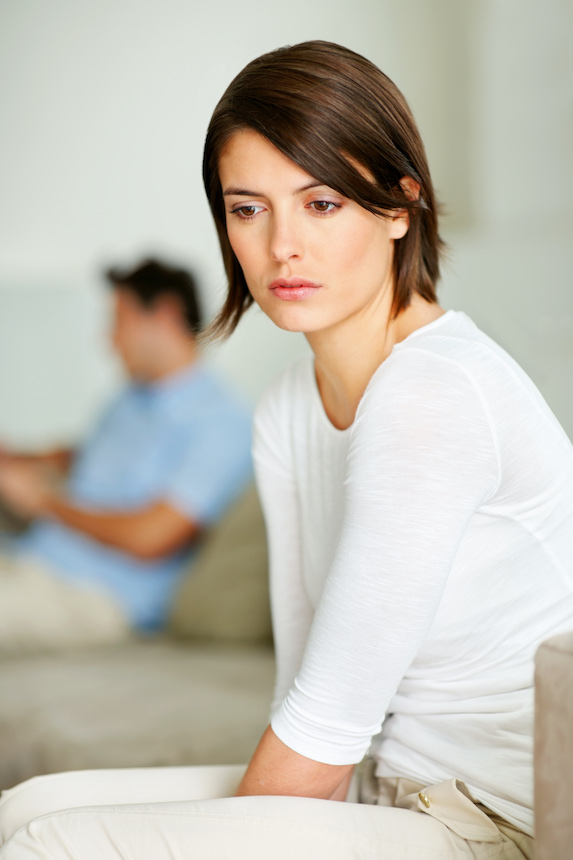 Woman sits looking frustrated as he husband sits in the background