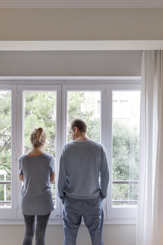 Couple stands facing a window, rear view