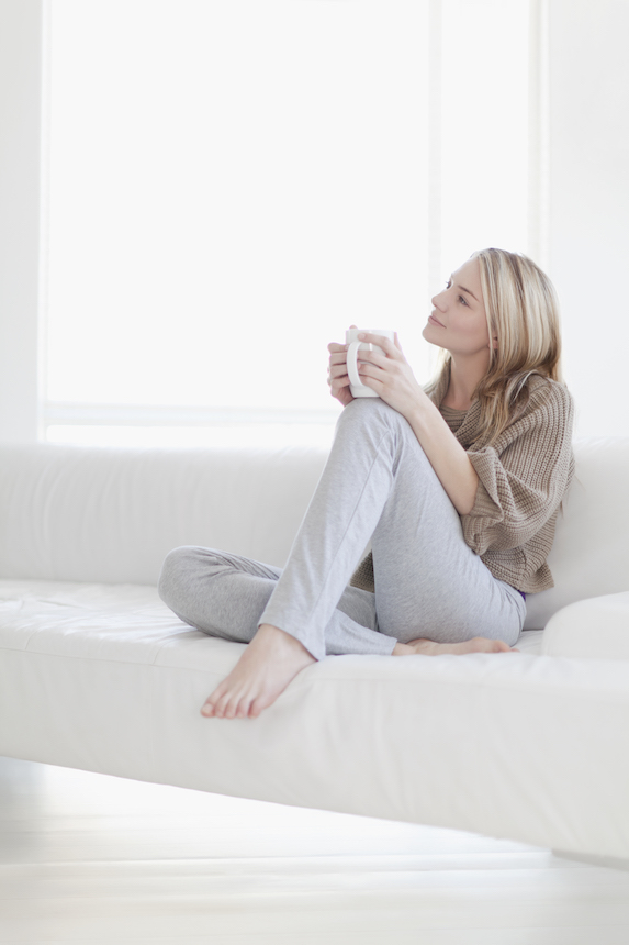 Woman sits having a cup of coffee at home