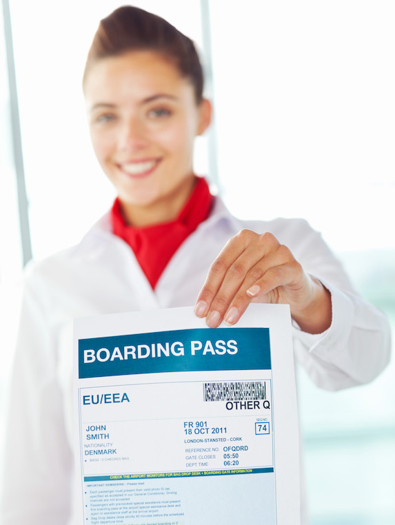 Cabin crew member holds up a boarding pass