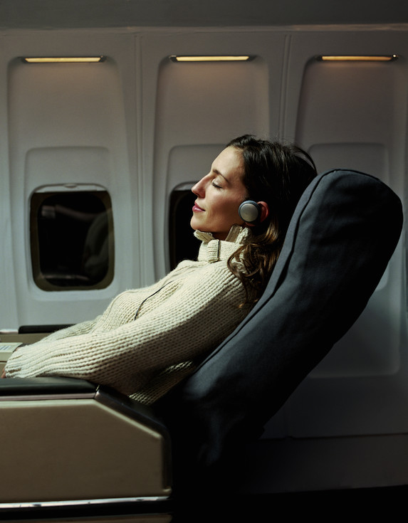 Woman wearing headphones on a flight reclines comfortably in her seat