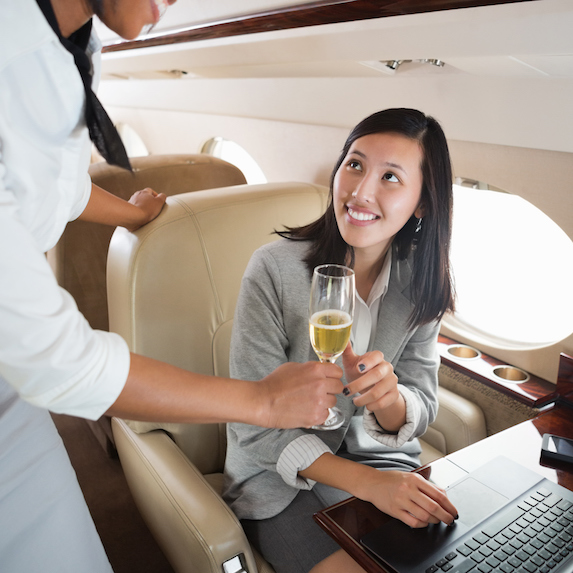 Woman being offered champagne on a flight