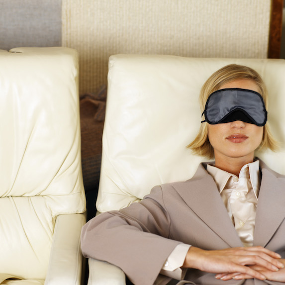 Professional-looking blonde woman wearing a sleep mask relaxes in first class on a flight