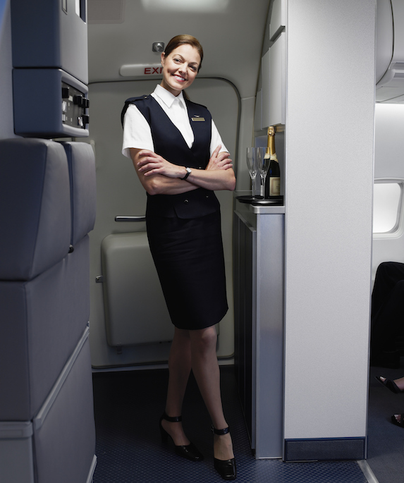 Flight attendant smiles in plane galley with a bottle of champagne nearby