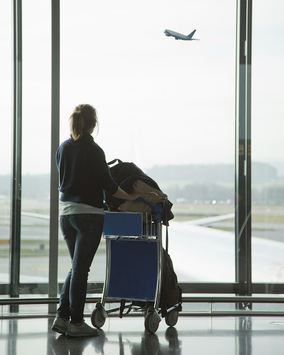 Woman with luggage trolley watches a plane takeoff as she stands in the airport