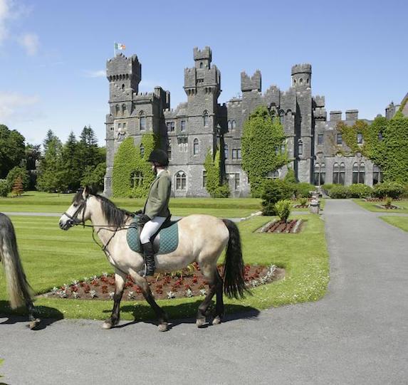 Riding horseback past the front exterior of Ashford Castle