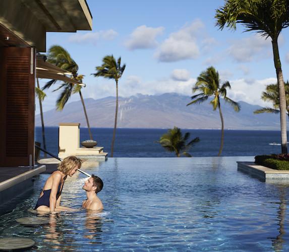 A couple enjoy the pool at The Four Seasons Maui