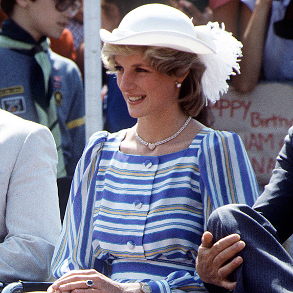 Princess Diana seated wearing blue, white and yellow striped dress