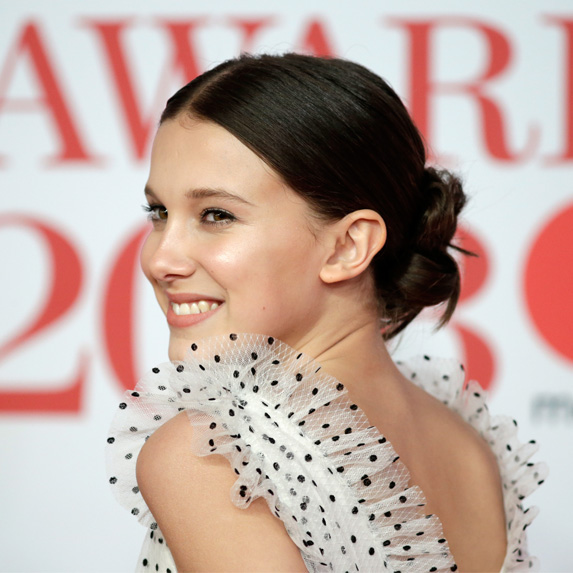 Millie Bobby Brown looking over her shoulder and smiling