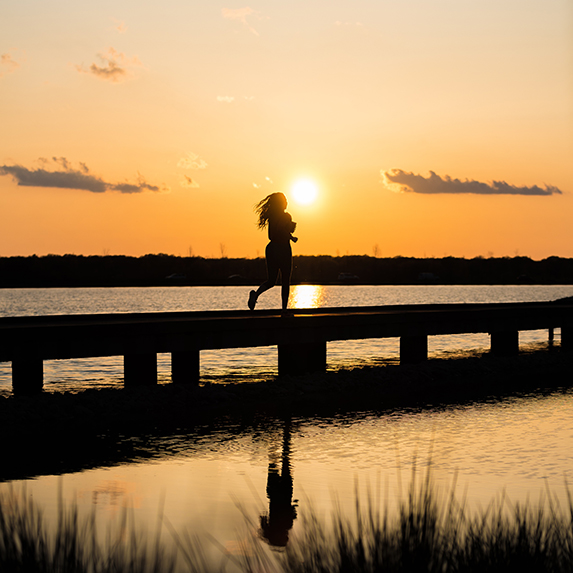 woman running against sunset