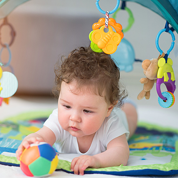 Baby on tummy playing with ball on activity mat