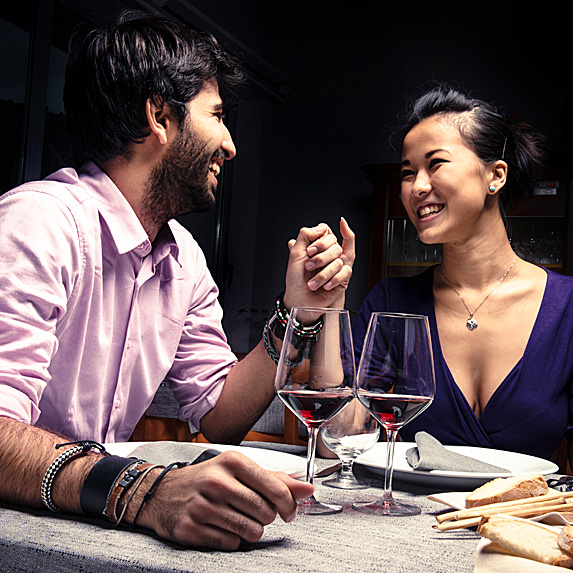 Man and woman holding hands during dinner date